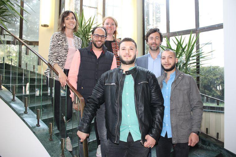 Schepen Silke Beirens, Fie Velghe van Refu Interim en gemeenteraadsvoorzitter Wouter De Vriendt bij drie nieuwkomers die een vrijwilligersjob kregen.