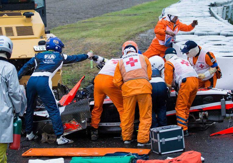 Reddingswerkers zijn bezig Jules Bianchi uit zijn Formule-1-wagen te halen. Links de kraanwagen waar hij tegen op knalde nadat hij van de baan was geraakt op een plek waar veel water lag. Beeld epa