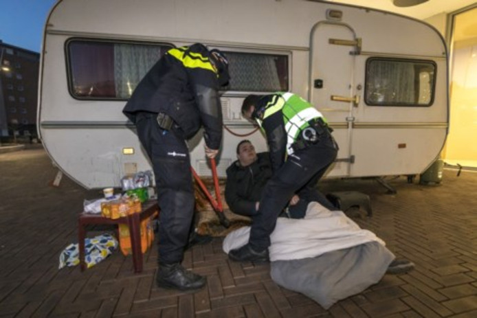 Agenten knippen de ketting kapot waarmee Willem Soering zich aan zijn caravan vastgeklonken heeft.