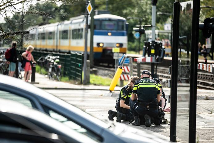 De verwarde jongeman wordt door de politie in de boeien geslagen op het station in Rheden.