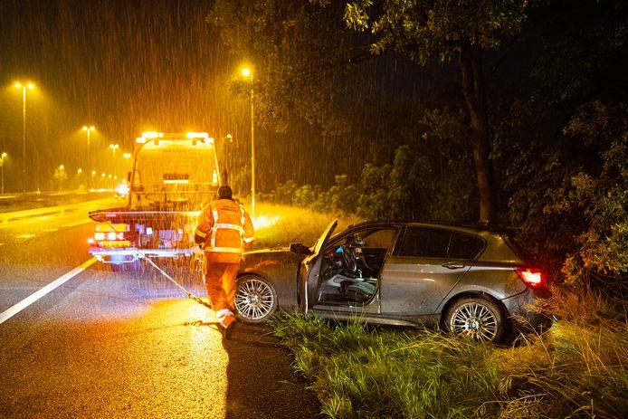 Zware regenval op de A50 bij Heerde: deze auto gleed van de weg als gevolg van de weersomstandigheden.