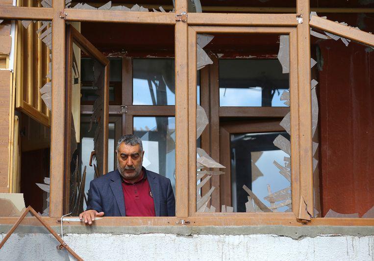 Een man bekijkt de schade in zijn flat in Terter (Azerbeidzjan) na een Armeense artillerie-aanval tijdens de gevechten om de regio Nagorno-Karabach. Beeld AP