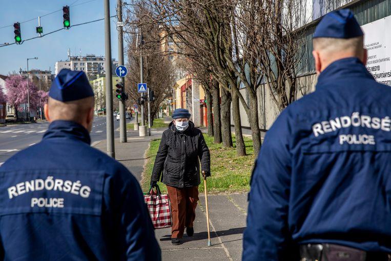 Politieagenten lopen langs een oudere vrouw in Bekescsaba, Hongarije. De dodelijkheid van covid-19 verschilt enorm tussen leeftijdsgroepen. Beeld EPA