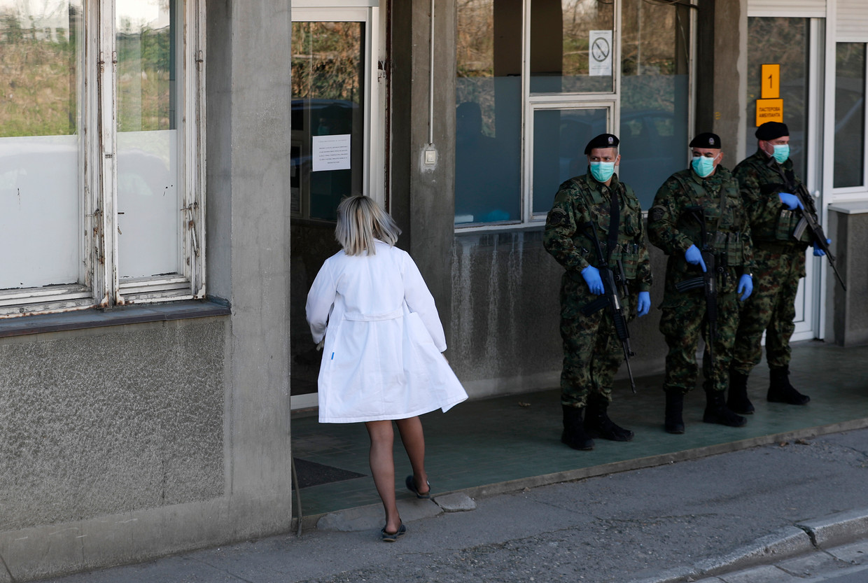 Servische soldaten bewaken de ingang van de kliniek voor infectie en tropische ziekten.