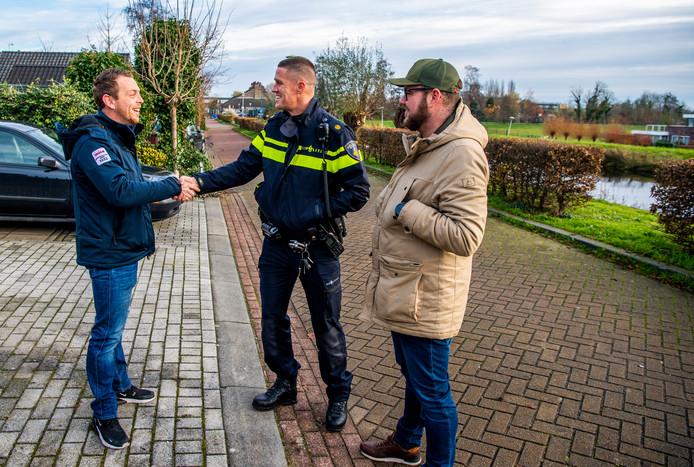 Wijkagent Anthony Coli maakt kennis met bewoner Aaron Dros (links), naast hem Bart Fioole (rechts).