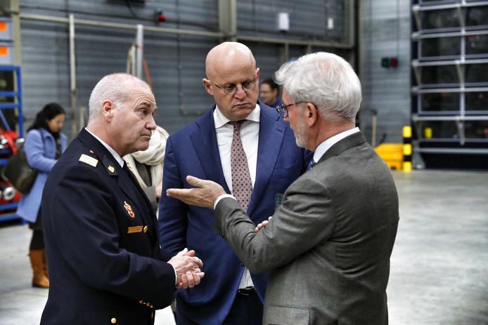 Minister Ferdinand Grapperhaus (midden) wordt bijgepraat door burgemeester Jac Klijs (rechts) van de gemeente Moerdijk en  Nico Koolen, strategisch manager Moerdijk bij Veiligheidsregio Midden- en West-Brabant.