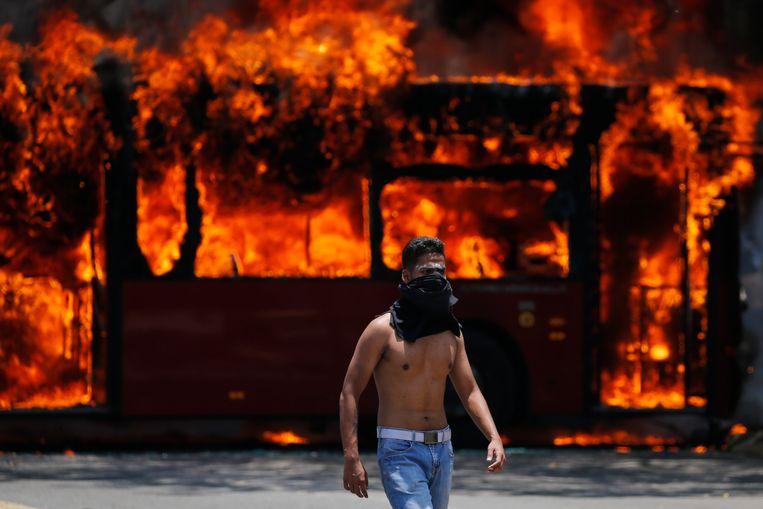 Een demonstrant loopt in Caracas voor een bus langs die in brand is gestoken door demonstranten.