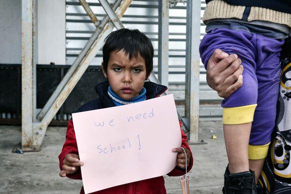 Een kind houdt een bordje omhoog met de tekst 'we hebben school nodig' in een migrantenkamp in Athene. Archieffoto.