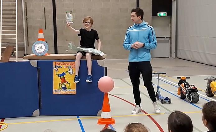 Jurre van Dijk, winnaar Sjors Sportief-tekenwedstrijd, krijgt eerste boekje van Jerome de Clercq van SSNB