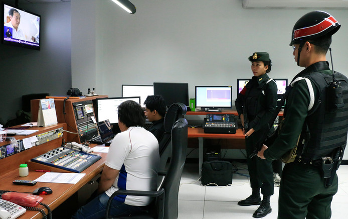 Soldaten controleren journalisten van de publieke omroep in Thailand.