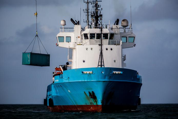 Een bergingsschip takelt een lege container van het schip Blue Bella om overboord geslagen puin van de MSC Zoe te bergen. Het containerschip MSC Zoe verloor in de nieuwjaarsnacht 281 containers in de Noordzee toen het de verkeerde zeevaartroute boven de Waddeneilanden pakte.