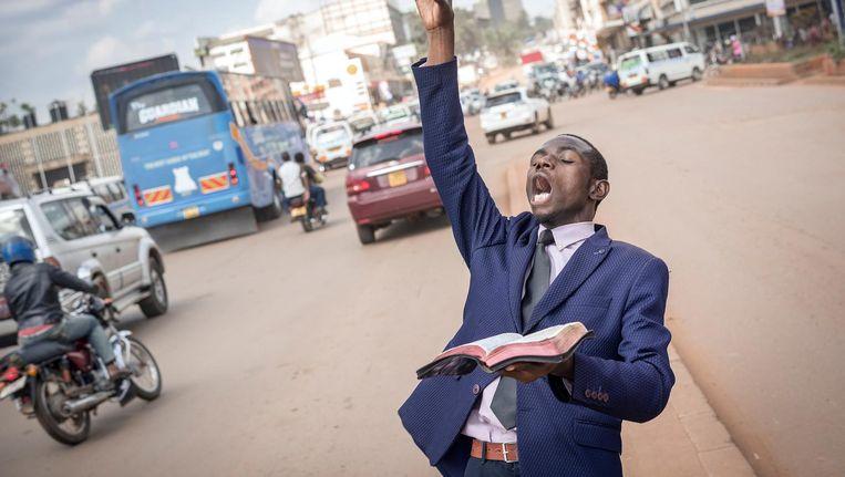 Straatpredikant Said Aminadabu tijdens de ochtendspits in de Oegandese hoofdstad Kampala. `Ik ben een evangelist, zoals Lucas.' Beeld Sven Torfinn / de Volkskrant