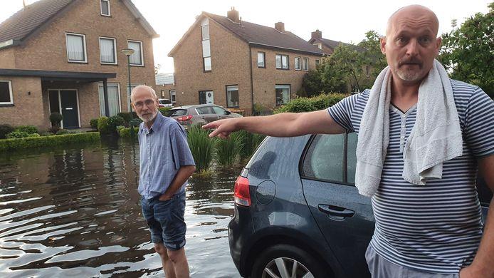 Jacques Baeten  (links) en Henk van Dijk, buren in Hoefakker in Chaam. De straat is volledig ondergelopen, hun woningen hebben ook forse waterschade opgelopen.