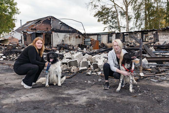 Thirza Lindeboom (links) en Kalijn Groenenberg zijn een doneeractie begonnen voor de door brand getroffen hondenfokker Martin Visscher. Op de achtergrond de vorige week in de as gelegde schuur.
