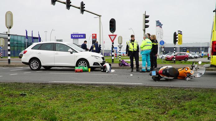 De scooter ligt vooraan de weg. Hulptroepen praten over het ongeluk.