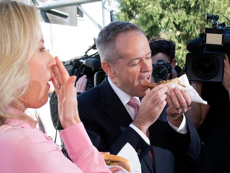 Labour-leider en kandidaat-premier Bill Shorten en zijn vrouw Chloe eten vandaag naar goede traditie een typische hot dog op verkiezingsdag in Melbourne.