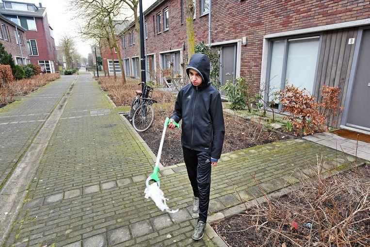 Ilias Driouchi van het Wellantcollege ruimt in zijn eigen wijk zwerfvuil op.  Foto Guus Dubbelman / de Volkskrant Beeld