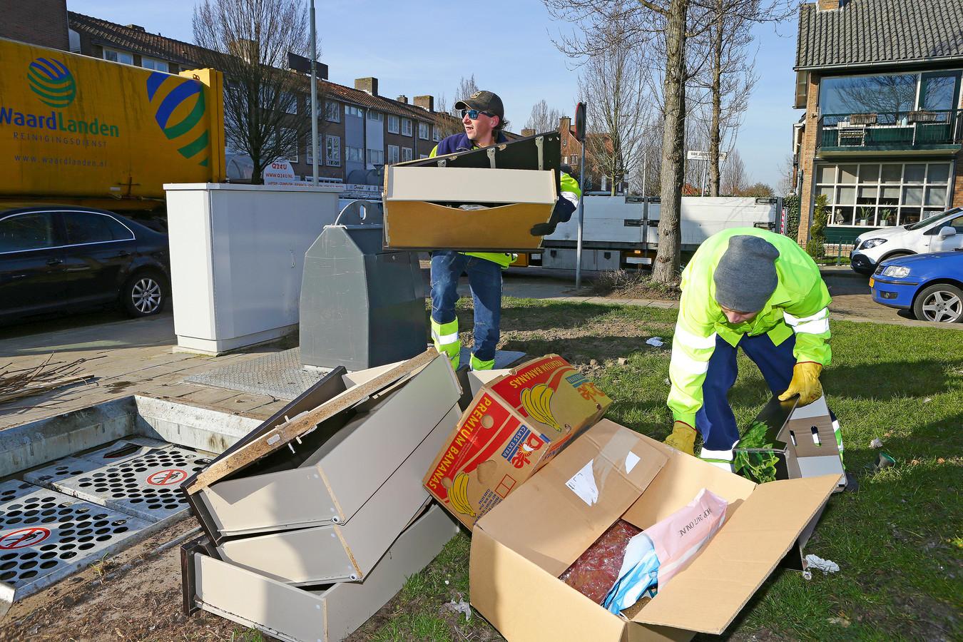 Medewerkers van Waardlanden ruimen afval bij een wijkcontainer op.