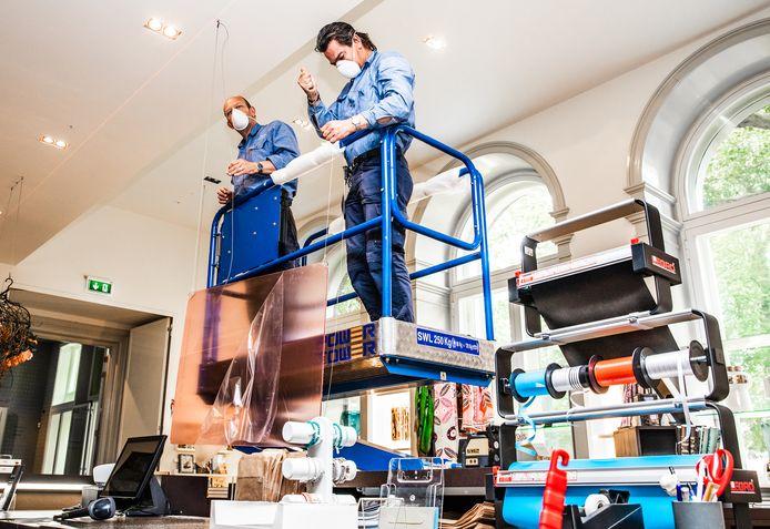 In het Dordrechts Museum hangen medewerkers spatschermen op bij de kassa in de museumwinkel.