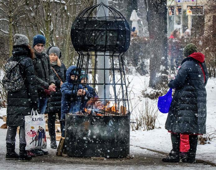 Passanten in het Sokolniki-park in Moskou warmen zich aan een publieke vuurkorf. Foto Mladen Antonov