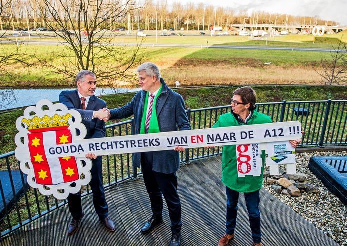 Nico Voogt overhandigt samen met Gouds CDA-raadslid Martijn van der Wind een uit de kluiten gewassen sleutel aan CDA-Kamerlid Chris van Dam om angst voor op slot gaan van Goudse Poort de op en afrit van de A12 onder de aandacht te brengen.