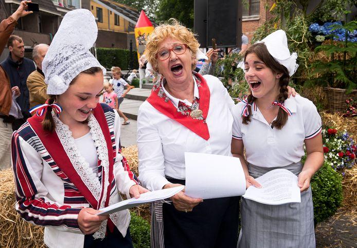 Graskaasdag 2018 op het Kerkplein: de kaasmeisjes zingen uit volle borst mee met het Kaaslied.