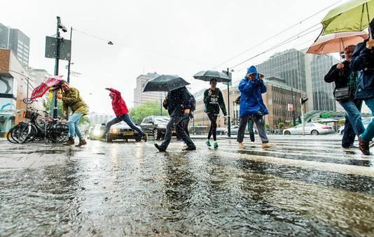 Rotterdammers banen zich een weg over de Coolsingel tijdens de regenval.