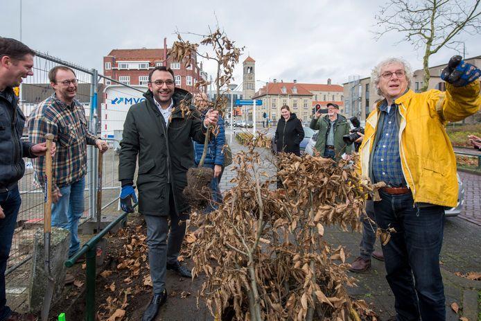 Wethouder Yasin Torunoglu (links) en Harry Janssen van de buurtvereniging halen beukenhaagjes weg bij het Vogelzangterrein en planten ze bij het Lodewijk Napoleonplein in Eindhoven.