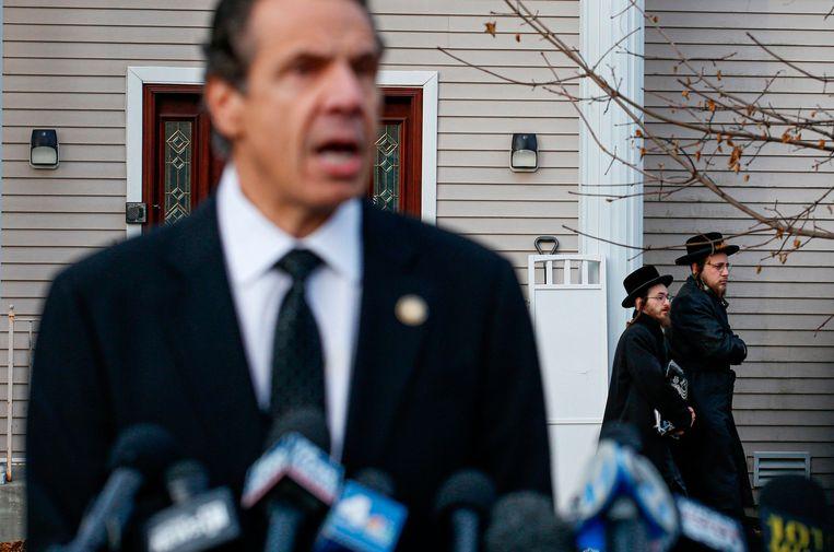 Andrew Cuomo, gouverneur van de staat New York, staat de pers te woord buiten het huis van rabbijn Chaim Rottenberg, in het plaatsje Monsey. Een man stak daar zondag vijf mensen neer. Cuomo spreekt van een 'binnenlandse terroristische daad'. Beeld AFP