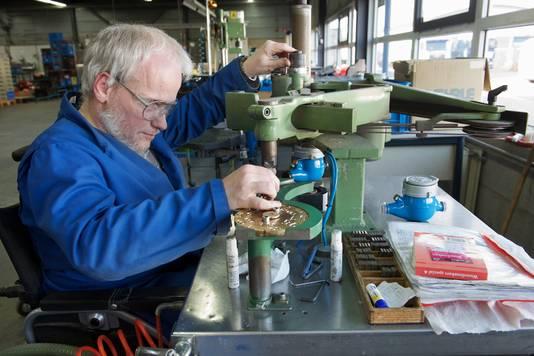 Een werknemer van Presikhaaf Bedrijven in Arnhem aan de slag met de montage van watermeters.