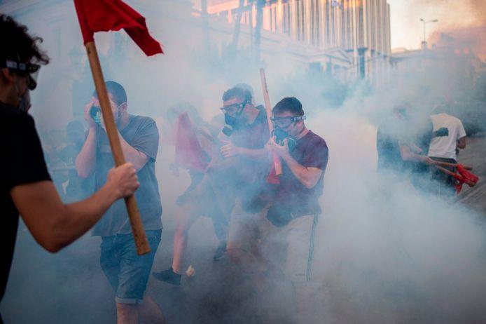 Demonstranten lopen door traangas.