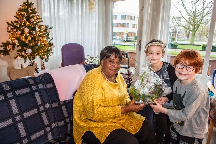 Karlijn (rechts 7 jaar) en Julia ( links 6 jaar) geven een zelf gemaakt kerststuk aan bewoonster van Savelberg mevrouw Marléne Vilt (76).