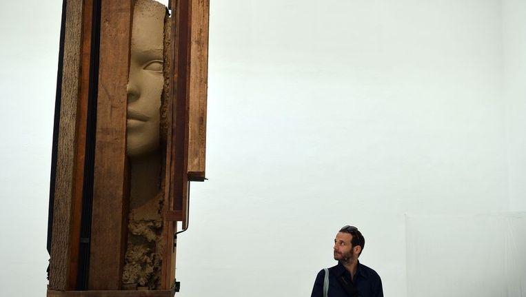 Een bezoeker bekijkt het werk van Mark Manders in het Nederlands paviljoen tijdens de Biënnale van Venetië Beeld afp