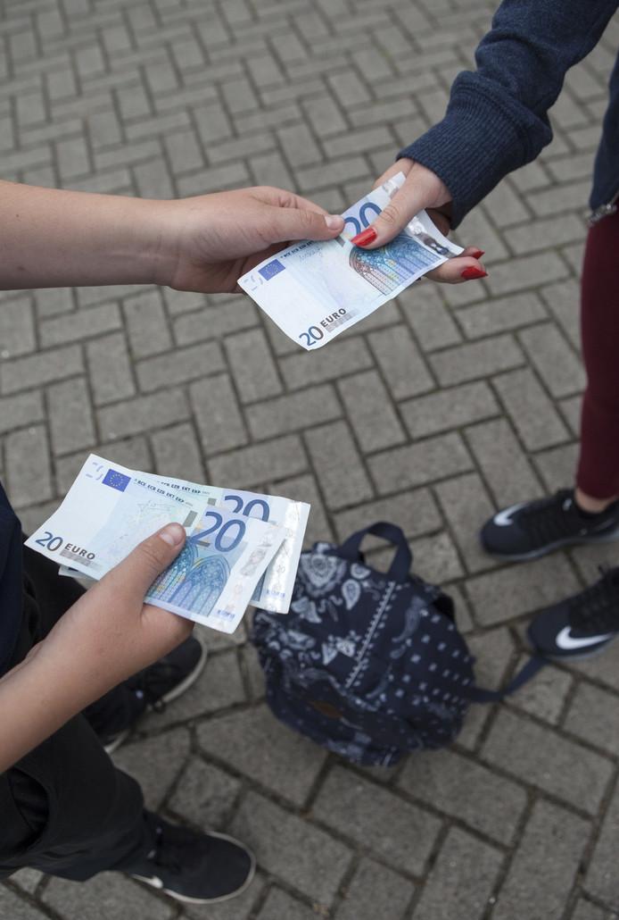 Het verhandelen van vals geld op school.