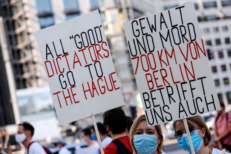 Een pro-Wit-Russische demonstratie, zaterdag, in Berlijn. Op de borden staat: 'Alle 'goede dictators gaan naar Den Haag' en 'Geweld en moord, 700 km van Berlijn, gaat ook ons aan'.   Beeld EPA