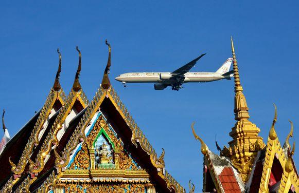 Een vliegtuig van Etihad vliegt over de Lat Krabang tempel nabij Bangkok. Illustratiebeeld.
