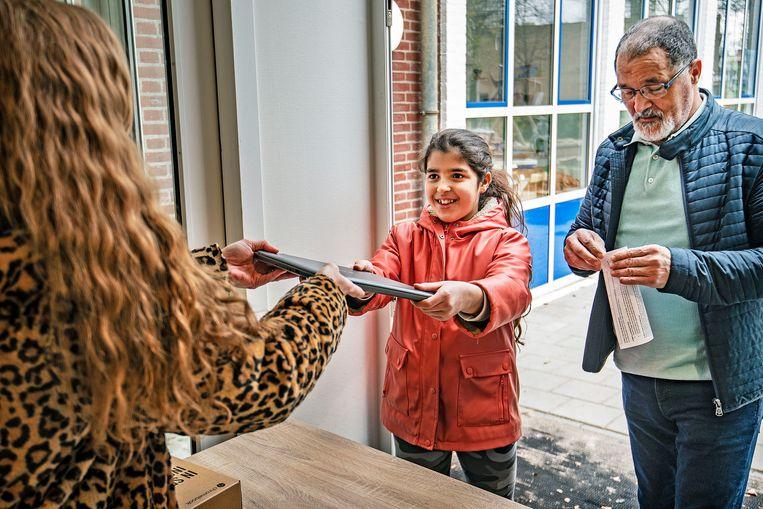 Op de Dalton basisschool Louis Bouwmeester worden laptops aan ouders en leerlingen in bruikleen gegeven. Omdat scholen gesloten zijn, krijgen leerlingen les via internet.  Beeld Guus Dubbelman / De Volkskrant
