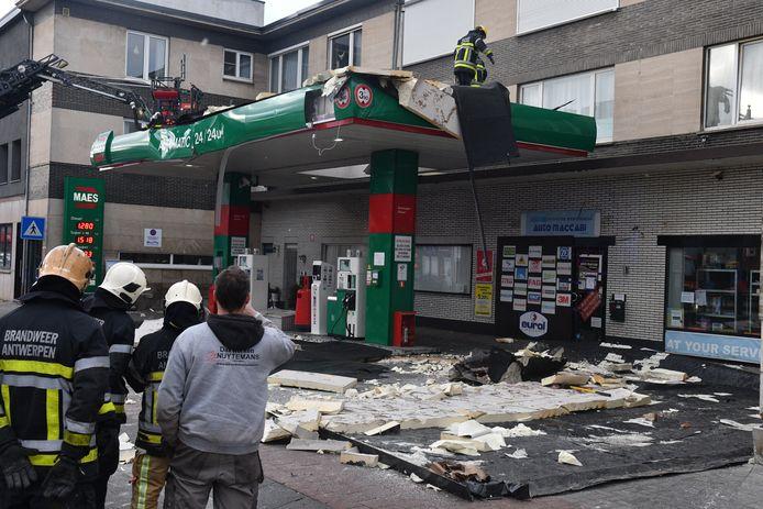 Brandweermannen meten de schade op aan een tankstation in Hoboken.