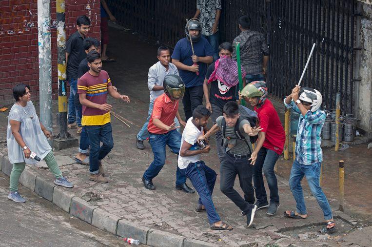 Een fotojournalist gaat ervandoor als een groep mannen hem aanvalt tijdens demonstraties voor veiliger wegen.  Beeld EPA/Monirul Alam