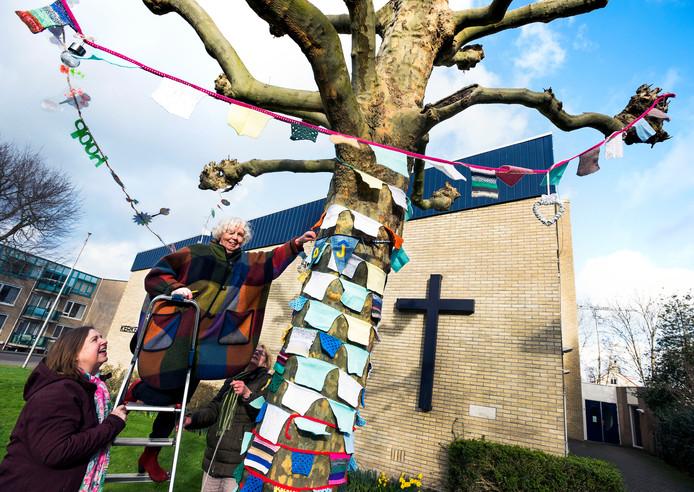 Dinie Schipper hangt gehaakte vlaggetjes in de feestboom. De vlaggetjes zijn gemaakt in samenwerking met de kerkelijke gemeente. Ieder die zijn of haar vlaggetje in de boom opgehangen wil hebben moet hiervoor een financiele bijdrage leveren. Het eindbedrag is bestemd voor een te realiseren zorgboerderij in de Oekraïne.