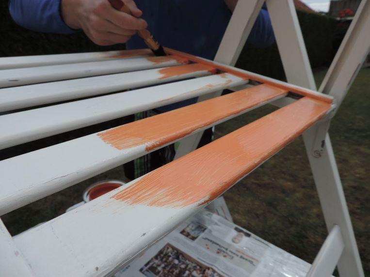 De stoel wordt in het oranje geverfd