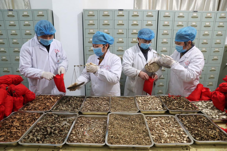 Medewerkers van een ziekenhuis voor traditionele Chinese geneeskunde bereiden zakjes kruiden voor patiënten met het nieuwe coronavirus.