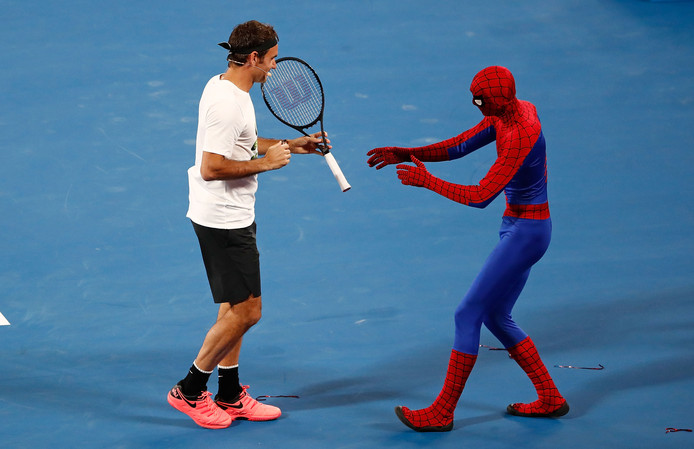 Roger Federer geeft Spider-Man zijn racket bij de jaarlijkse kidsdag voor de start van de Australian Open.