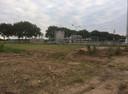 Een strook grond waar de maïs weggehaald, met op de achtergrond de installatie van Vermilion.
