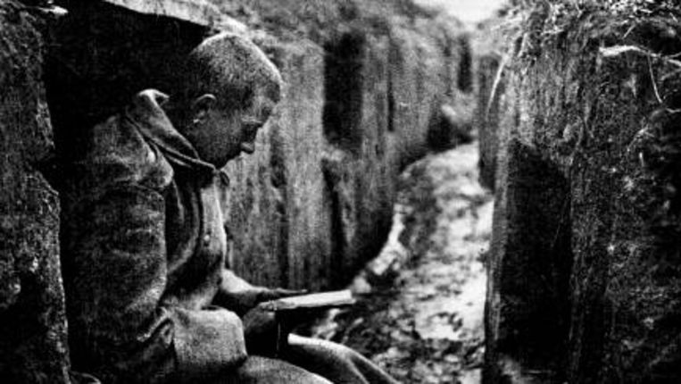 Een Oostenrijkse soldaat leest in een loopgraaf in Frankrijk zijn ochtendgebed. (André Kertész) Beeld