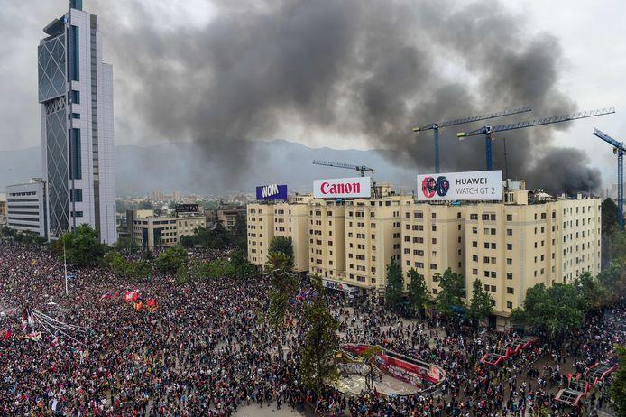 Rook van de brand in het universiteitsgebouw waait over het centrum van de Chileense hoofdstad Santiago, waar honderdduizenden protesteren tegen het regeringsbeleid.