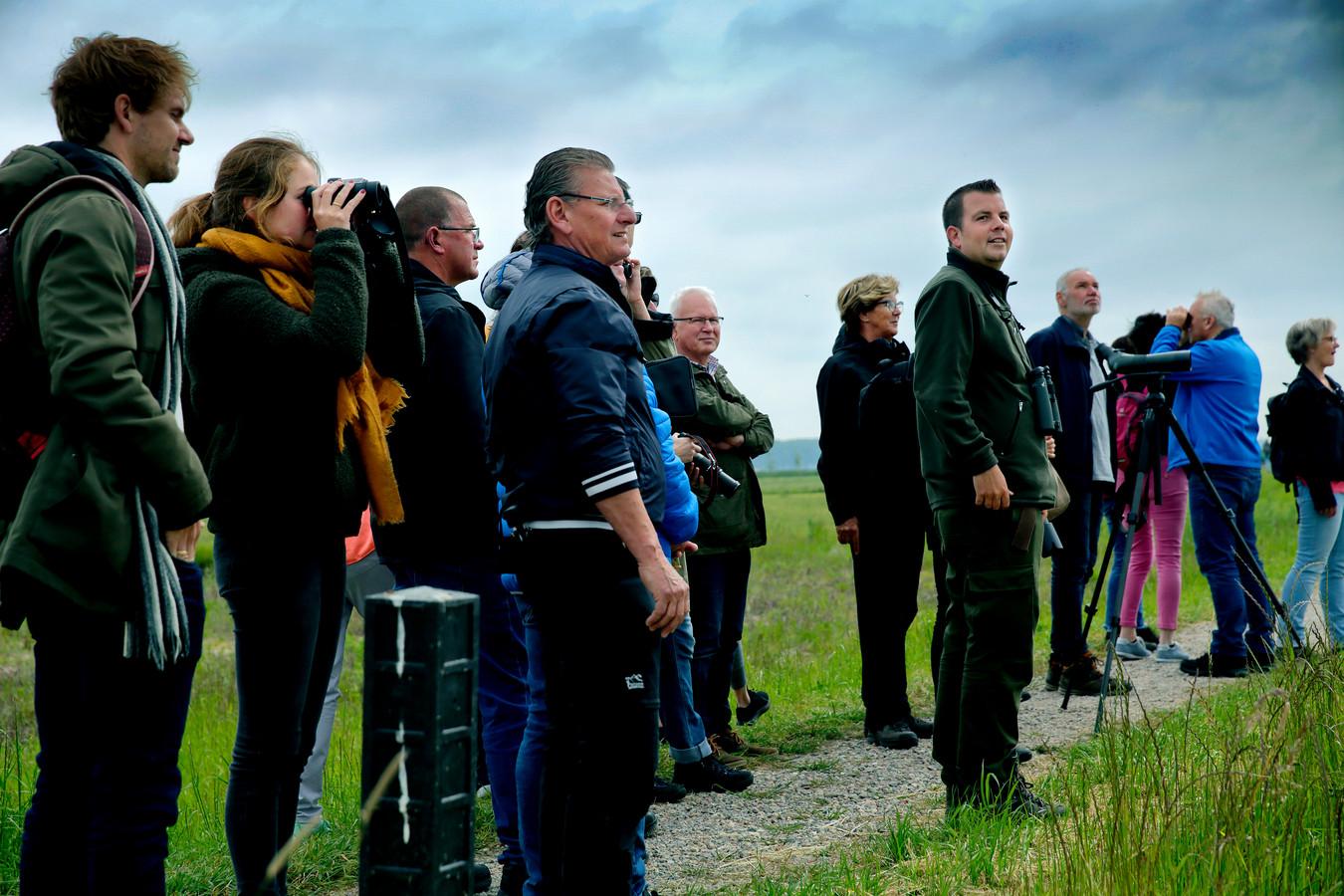 Tientallen mensen haken aan bij boswachter Thomas van der Es die bij de opening van de Nieuwe Dordste Biesbosch een vogelexcursie geeft.