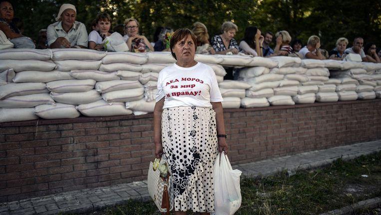 'Vadertje Winter voor vrede en waarheid', staat op het T-shirt van deze vrouw voor de ingang van het rebellenhoofdkwartier. Beeld Foto AFP