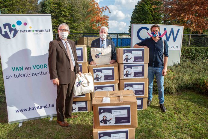 Algemeen directeur Stephan Verwee en voorzitter Walter De Donder van Haviland overhandigen de maskers aan Wim Van Campenhout (rechts), adjunct-directeur van het CAW.