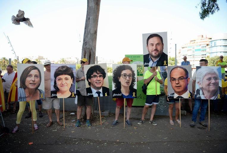 Mensen houden tijdens een demonstratie borden omhoog van Catalaanse leiders die zijn verbannen of in de gevangenis zitten. Van links naar rechts: Carme Forcadel, Anna Gabriel, Carles Puigdemont, Marta Rovira, Oriol Junqueras, Jordi Turull and Clara Ponsati.  Beeld AFP